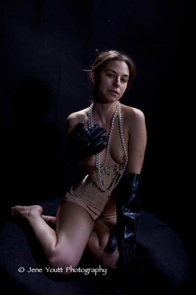 female nude wearing pearls & black gloves