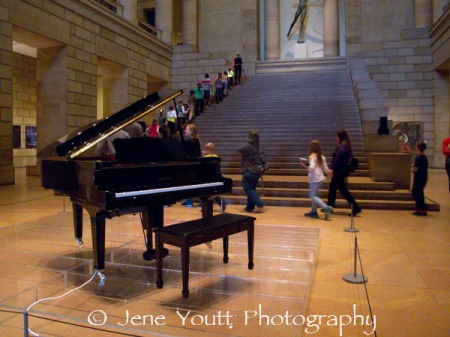 school children on grand staircase with cage piano
