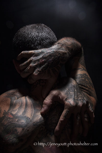 Tattooed male grasping his head and shoulders.
